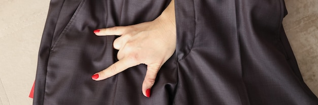 Woman hand showing goat gesture through fly of men trousers closeup