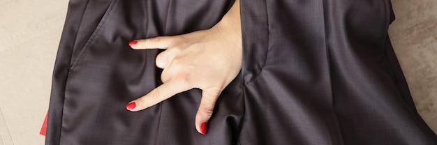 남자 바지 근접 촬영의 비행을 통해 염소 제스처를 보여주는 여자 손