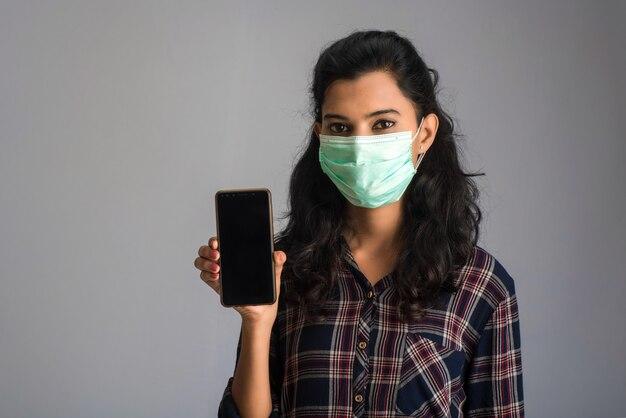 Рука женщины показывая умный мобильный телефон с лицевой маской безопасности медицинской для предотвращения концепции coronavirus или covid19, здравоохранения и инфекции