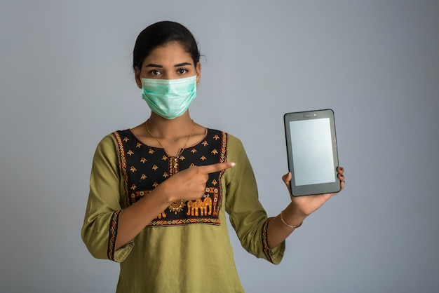 Рука женщины показывая умный мобильный телефон с концепцией лицевой маски безопасности, здравоохранения и концепции инфекции