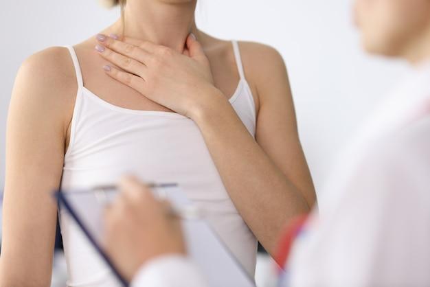 医師の予約のクローズ アップで首の痛みを示す女性の手