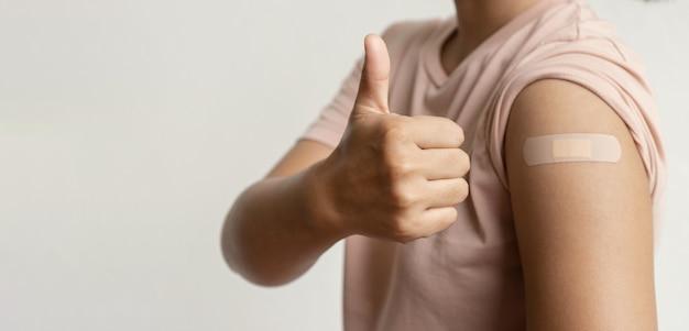 엄지손가락을 치켜드는 여성 손이 붕대로 코로나바이러스 covid19 어깨에 예방접종을 하러 갔다