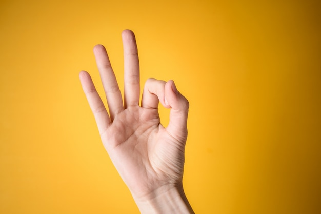 Woman hand shows gesture okay on yellow background