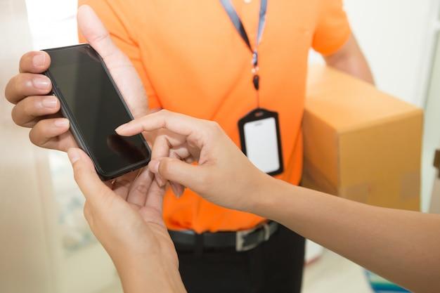 配達員からの箱の配達を受け入れると携帯電話でサインインする女性の手
