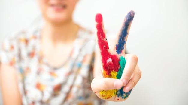 여자 손, 고립 된 여러 가지 빛깔의 페인트로 얼룩져 있습니다.