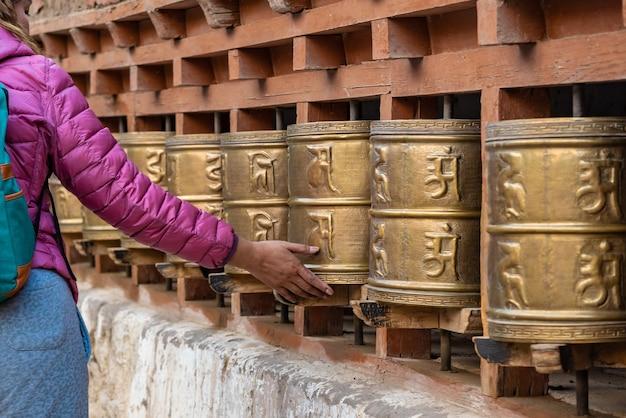 Woman hand spinning tibetan buddhist prayer wheels , india.