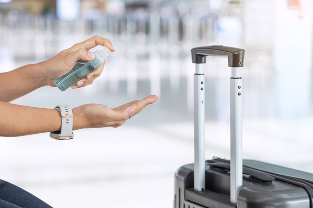 Woman hand spraying alcohol sanitizer after holding handle luggage bag in airport terminal