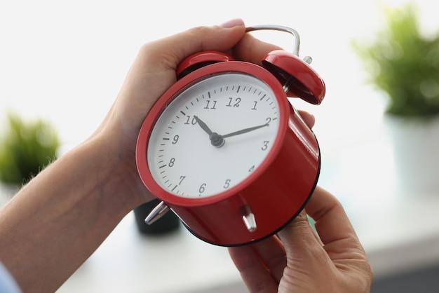 Женщина рука запускает красный будильник крупным планом