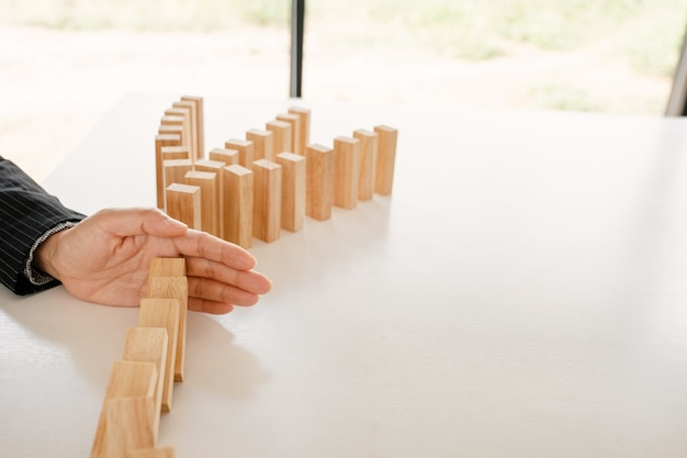 Woman hand stop wooden blocks for protect other block concept risk of management and strategy plan