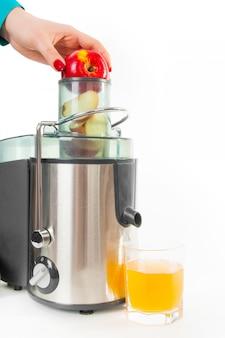 女性の手はリンゴを取る。ジュース抽出器、白で隔離される絞りたてのリンゴジュース