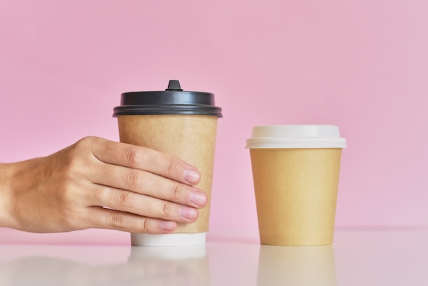 Woman hand take on of two coffee paper cup on pink background