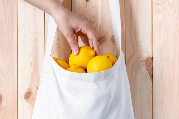 女性の手は木製の壁にテキスタイルエコバッグからレモンを取ります