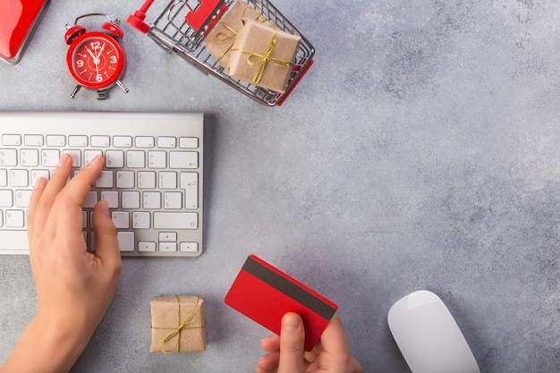 Woman hand takes credit card, other hand is on keyboard