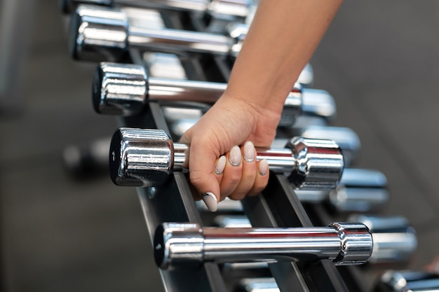 Woman hand takes dumbbell form rows of dumbbells in the gym