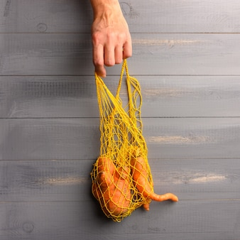 Woman hand takes eco friendly string bag with ugly carrot on the wooden surface