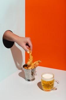 Женская рука берет жареные креветки в металлическом ведре через бумажное отверстие. современное твердое теневое пиво высокого качества.