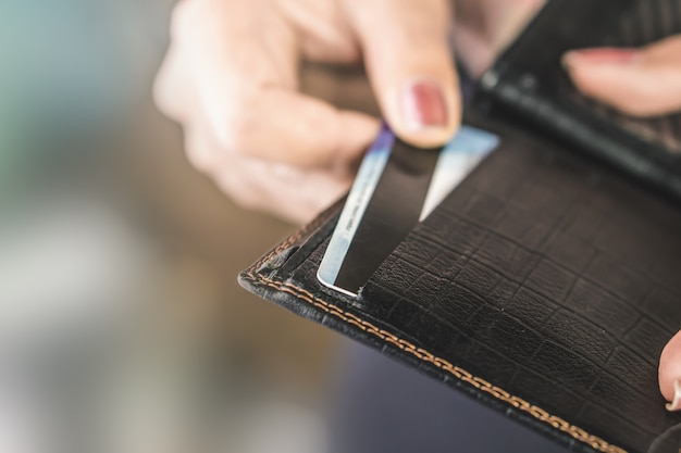 Woman hand taking credit card from black purse
