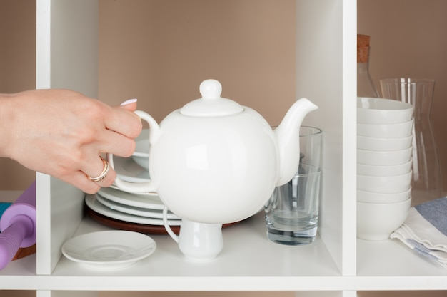 Woman hand taking dishware pieces from shelf in kitchen