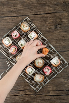 Woman hand taking one sushi roll from grilled basket on a wooden background .