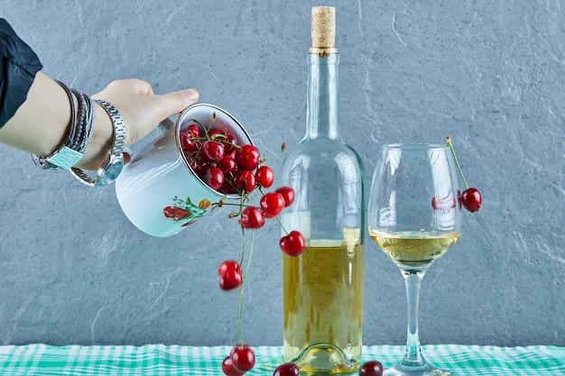 파란색 표면에 유리와 체리와 화이트 와인 한 병의 컵을 던지는 여자 손