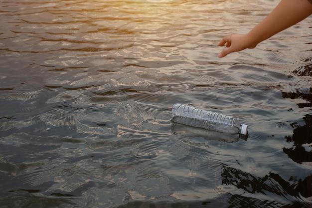 Женская рука, чтобы поднять использованную пластиковую бутылку для отходов на воде в канале