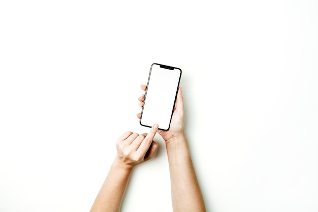 空白のスマートフォンの画面に触れる女性の手。フラットレイ、上面図のモックアップテンプレート。