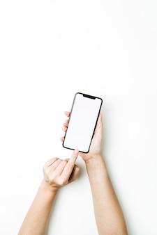 空白のスマートフォンの画面に触れる女性の手。上面図