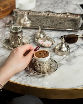 Woman hand next to turkish coffee served with water in turkish silver set