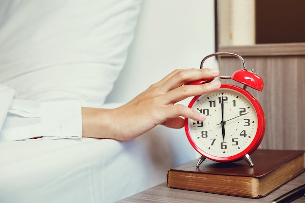 Woman hand turning off alarm  clock waking up at morning