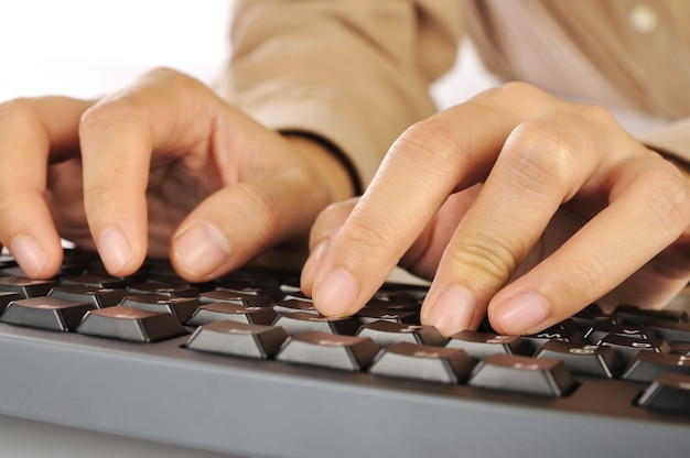 Woman hand typing on black computer keyboard isolated over white background