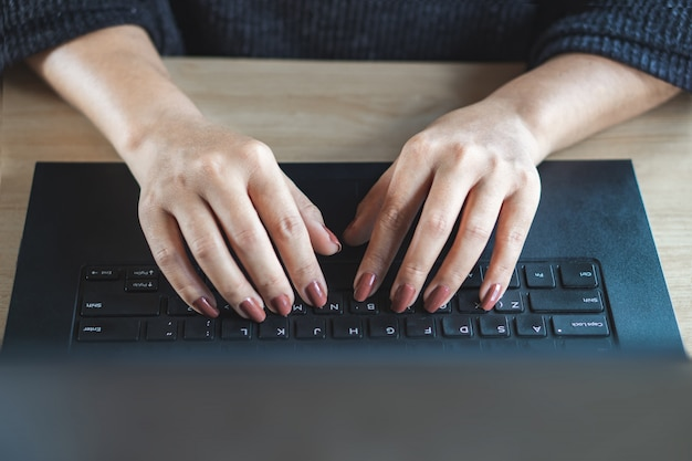 Woman hand typing on keyboard computer laptop
