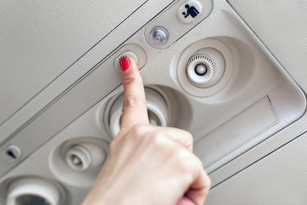 Woman hand up to adjust console panel at the air conditioner above the seat in cabin of low cost commercial airplane.