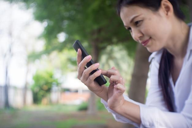 女性の手は幸せでスマートフォンを使用します。