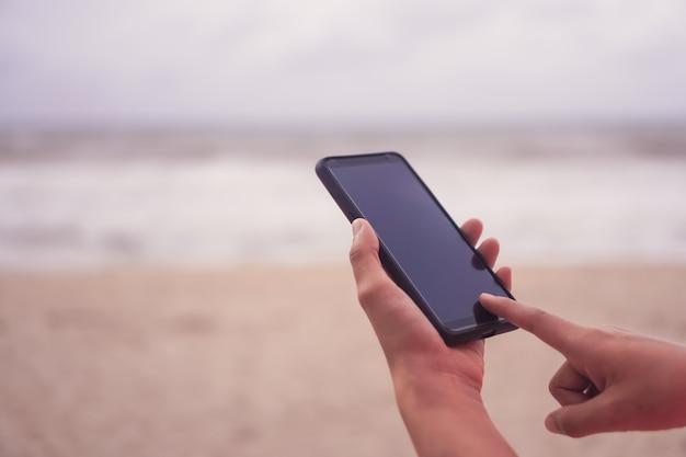 여자 손은 스마트 폰을 사용하여 비즈니스, 소셜 네트워크, 커뮤니케이션을 공개적으로 수행합니다.