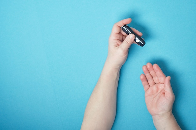 血糖値計、糖尿病、血糖、ヘルスケアの概念を使用して血糖値をチェックするために彼女の指にランセットを使用して女性の手。青い背景コピースペース上面図