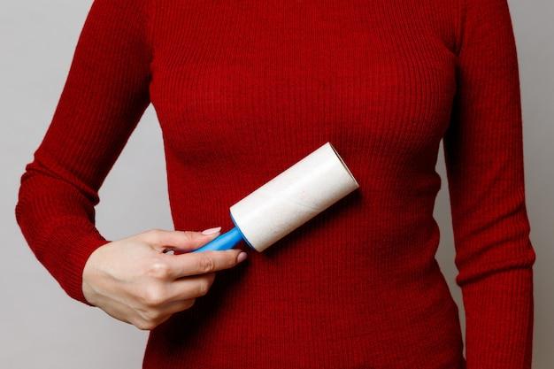 Женская рука с помощью липкого валика / средства для удаления ворса для чистки тканей