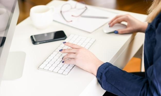 Рука женщины с помощью компьютера дома, в офисе. фото высокого качества