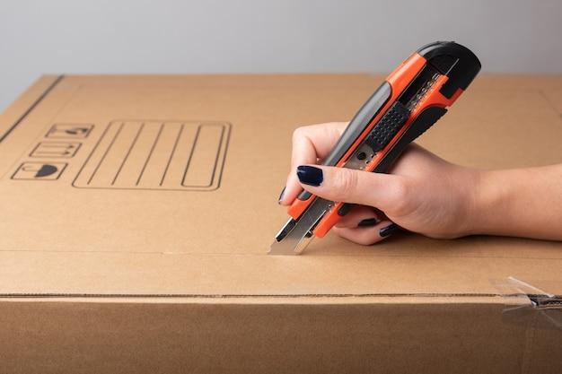 テキストやデザインなどのチュートリアル情報のコピースペースと段ボール箱にカッターナイフを使用して女性の手
