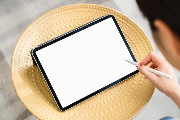デジタルタブレットを使用している女性の手と画面が空白です。