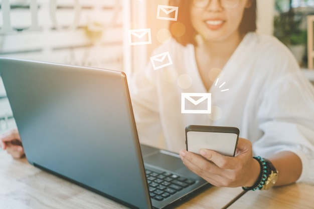 Рука женщины используя портативный компьютер для посылки и получения электронной почты для дела.