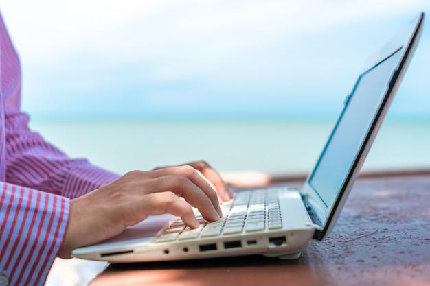 Рука женщины используя компьтер-книжку для работы изучает на столе работы с предпосылкой чистого пляжа природы внешней. бизнес, финансовая концепция.