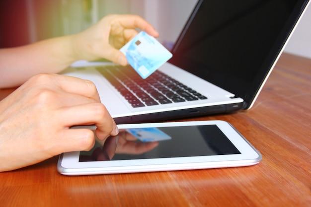 自宅でオンラインショッピングを支払う携帯電話を使用して女性の手