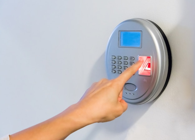 Woman hand using silver biometric scan with red fingerprint sensor