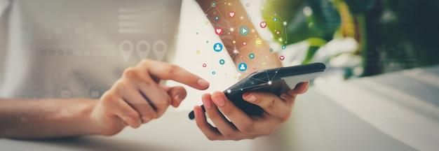 스마트폰을 사용하는 여자 손과 아이콘 소셜 미디어를 보여줍니다. 네트워크 기술 개념입니다.