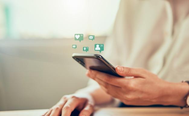 女性はスマートフォンを使用して手し、技術アイコンソーシャルメディアを表示します。コンセプトソーシャルネットワーク。 Premium写真