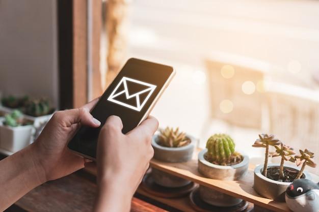 스마트 폰을 사용 하여 이메일을 보내고받는 여자 손.