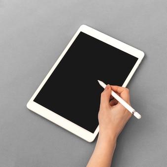 タブレット用のスタイラス鉛筆、空白の画面、ビジネスとオフィスのテーブルのコピースペースと銀の背景写真のモックアップを使用して女性の手