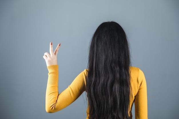 Знак победы рука женщина на сером фоне