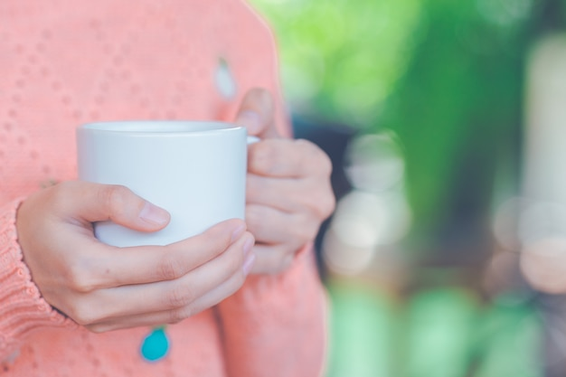 Woman hand in warm sweater holding a cup of coffee.