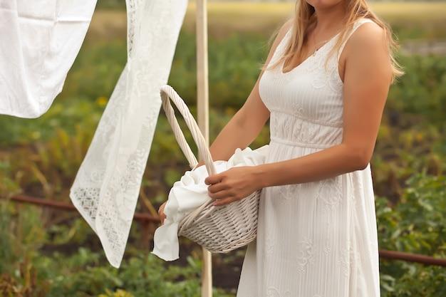 晴れた日に屋外で洗濯物を手洗いして吊るす女性。水のブリキのバケツを保持している女性。レトロなスタイル。